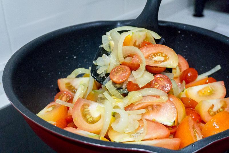 Mixing tomatoes and onions for Lemony Braised Chicken Legs