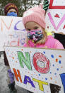 Anasofia Lopez, 5, of Grosse Pointe Park and her brother Joaquin Lopez, 8, left, stand with others prior to the start of the walking rally to protest against hate and racism in their neighborhoods Sunday, Feb. 21, 2021 in Grosse Pointe Park, Mich., following a white resident's display of a Ku Klux Klan flag in a side window facing their Black neighbor's home. JeDonna Dinges, 57, of Grosse Pointe Park, said the klan flag was hanging next door in a window directly across from her dining room. The incident occurred two weeks ago. (Clarence Tabb, Jr./Detroit News via AP)