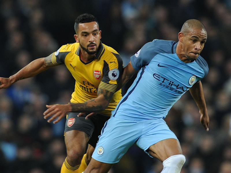 Theo Walcott and Fernando battle for the ball in this season's fixture at the Etihad: Getty