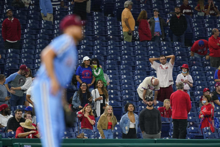 Fans reacts after Philadelphia Phillies pitcher Ian Kennedy, left, gave up a two-run home run to Colorado Rockies' Ryan McMahon during the ninth inning of a baseball game, Thursday, Sept. 9, 2021, in Philadelphia. (AP Photo/Matt Slocum)