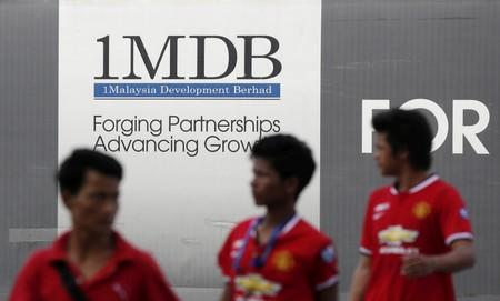 FILE PHOTO: Men walk past a 1Malaysia Development Berhad (1MDB) billboard at the fund's flagship Tun Razak Exchange development in Kuala Lumpur