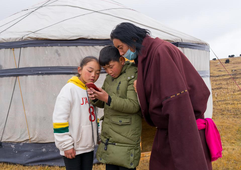 SOGZONG, CHINA - OCTOBER 29: Portrait of a tibetan nomad family living in a yurt in the grasslands and looking at a mobile phone, Qinghai province, Sogzong, China on October 29, 2017 in Sogzong, China. (Photo by Eric Lafforgue/Art In All Of Us/Corbis via Getty Images)