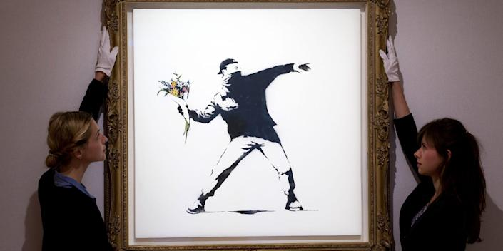 "Gallery assistants adjust ""Love is in the Air"" by British graffiti artist Banksy ahead of its sale at Bonhams auction house in London on June 24, 2013."