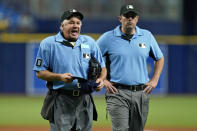 Home plate umpire Tom Hallion, left, makes Tampa Bay Rays relief pitcher Diego Castillo change his hat during the ninth inning of a baseball game Wednesday, June 23, 2021, in St. Petersburg, Fla. Looking on is first base umpire Mark Ripperger. (AP Photo/Chris O'Meara)