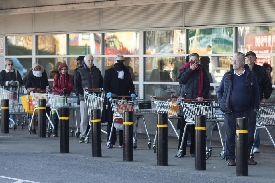 LONDON, ENGLAND, - MARCH 23: Shoppers queue outside a Sainsbury's supermarket ahead of opening on March 23, 2020 in London, England. Coronavirus (COVID-19) pandemic has spread to at least 182 countries, claiming over 10,000 lives and infecting hundreds of thousands more. (Photo by Dan Kitwood/Getty Images)