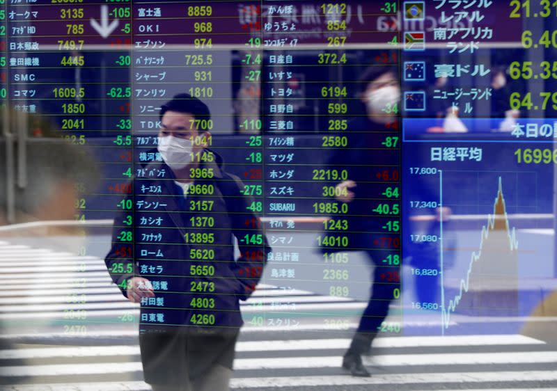 Passersby wearing protective face masks are reflected on a screen displaying stock prices outside a brokerage in Tokyo