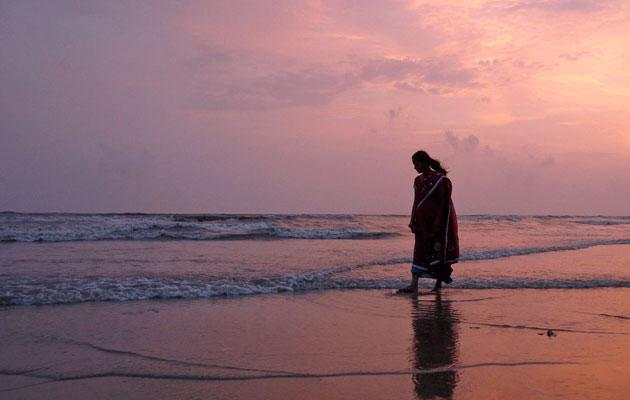 A woman walks at Juhu Beach as the sun sets in Mumbai July 6, 2012. REUTERS/Vivek Prakash