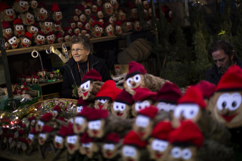 Sellers wait for customers inside their stall street as they sell Christmas-themed decorations in Barcelona downtown, Spain, Thursday, Dec. 20, 2012. Retail sales have been hammered in recent months as unemployment soars and consumers remain uncertain about whether European leaders are doing enough to combat the crisis. European countries are doing their best to encourage shoppers by lifting bans on stores opening on Sunday. (AP Photo/Emilio Morenatti)