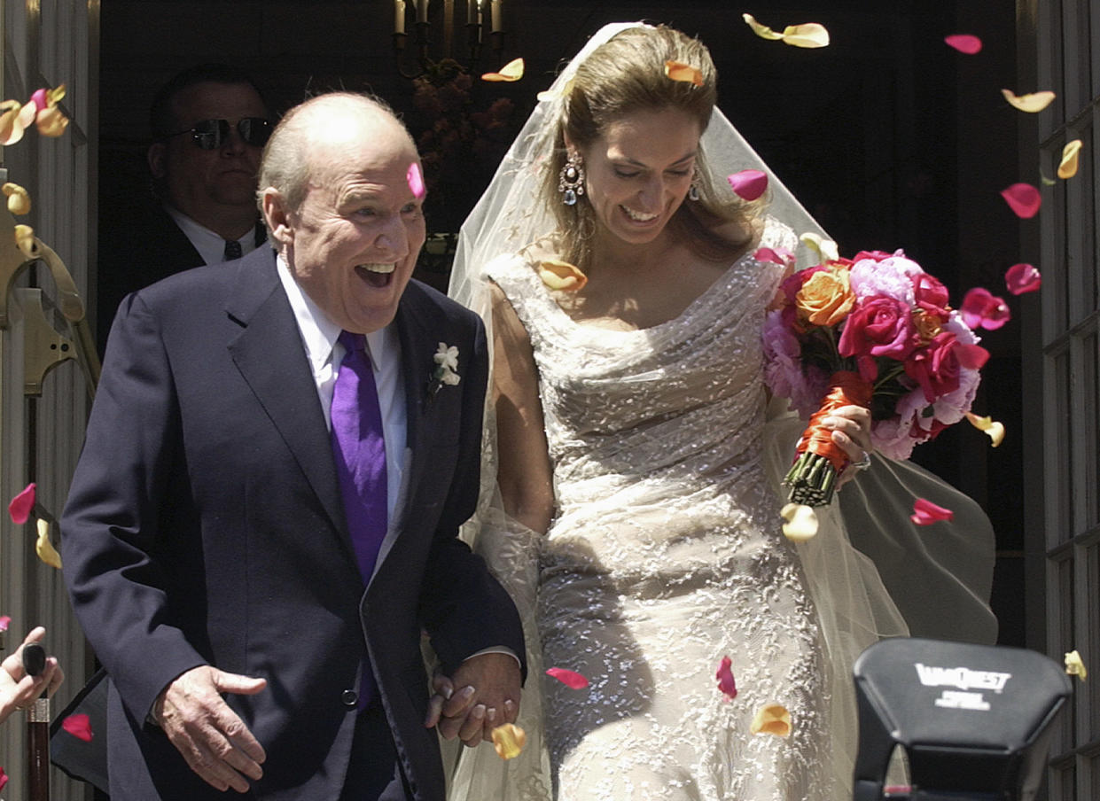 Former CEO of General Electric, Jack Welch (L), walks down the steps of Park Street Church with Suzy Wetlaufer after their wedding in Boston, Massachusetts, April 24, 2004. The couple met in October, 2001, while Wetlaufer was working on a story about Welch for the Harvard Business Review. REUTERS/Michael Dwyer  MAD/HB