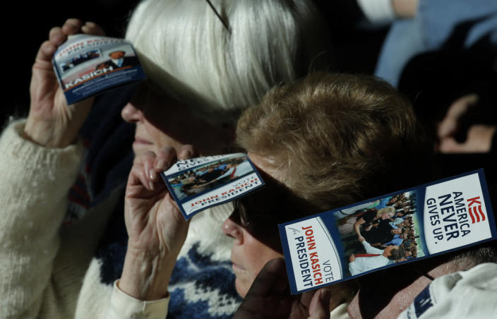 <p>Voters shield their eyes from the sun with pamphlets for Republican presidential candidate John Kasich as they listen to him speak during a town hall campaign event in Nashua, N.H., on Feb. 7, 2016. <i>(Photo: Mike Segar/Reuters)</i></p>