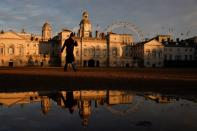 A man walks across Horse Guards Parade in the late afternoon in London
