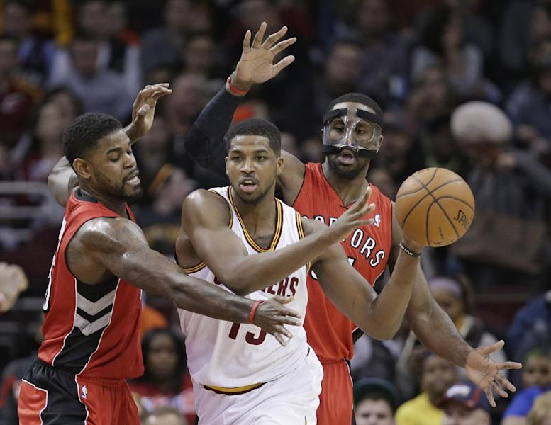 Toronto Raptors' Amir Johnson, left, and Patrick Patterson, right, put pressure on Cleveland Cavaliers' Tristan Thompson, from Canada, during the first quarter of an NBA basketball game, Tuesday, Feb. 25, 2014, in Cleveland. (AP Photo/Tony Dejak)