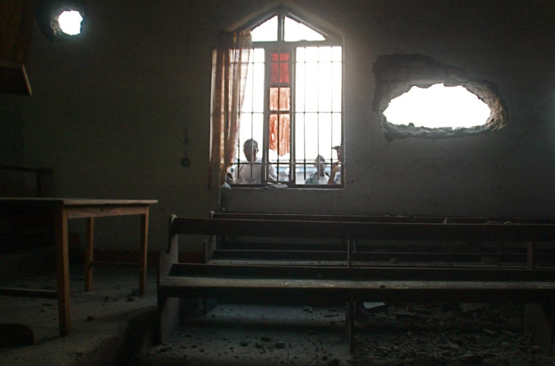 Kids look through the window of an Anglican church that was struck by mortars, wounding at least three according to one witness, in Goma, eastern Congo, Thursday, Aug. 22, 2013. Neighbors said at least five civilians were hit by mortar fire in Goma on Thursday during a second day of heavy fighting between government forces and M23 rebels to the north of the town. The violence marked the first reports of civilians being wounded inside the city since late May, and prompted the United Nations peacekeeping mission to issue a statement saying it would take the 'necessary steps to protect civilians.'(AP Photo/Joseph Kay)