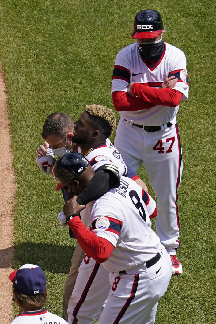 Chicago White Sox's Luis Robert (88) leaves with a team trainer and first base coach Daryl Boston as Chicago White Sox third-base coach Joe McEwing (47) watches during the first inning of a baseball game against the Cleveland Indians in Chicago, Sunday, May 2, 2021. (AP Photo/Nam Y. Huh)