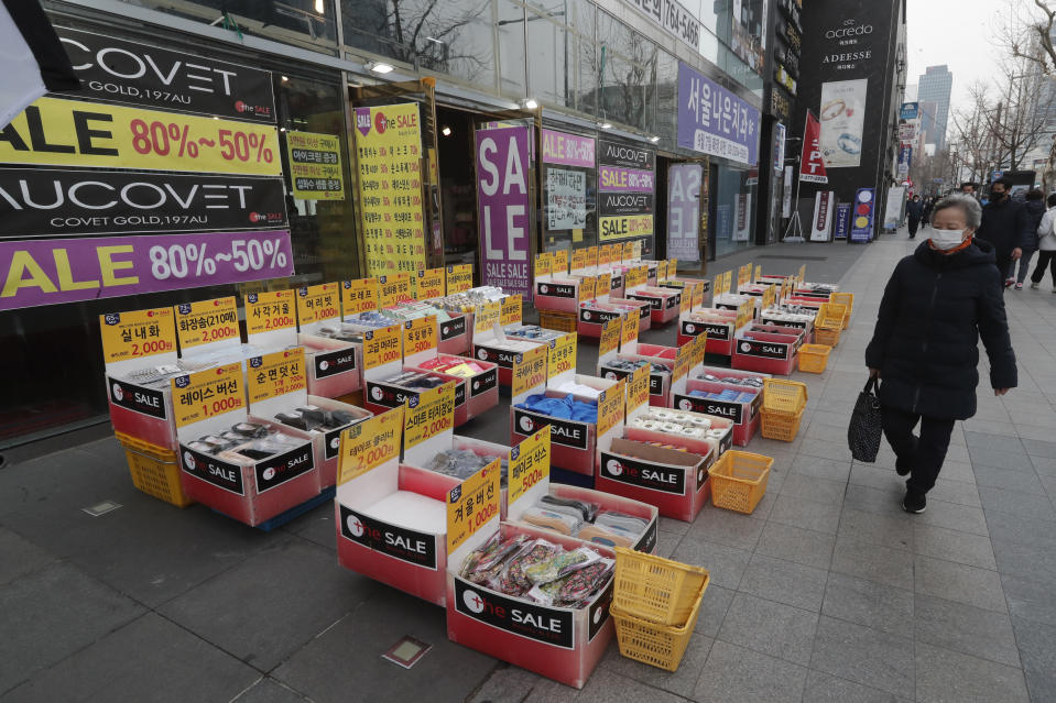 A woman wearing a face mask walks by a merchandise store in Seoul, South Korea, Thursday, March 4, 2021. South Korea's central bank says the country's economy shrank for the first time in 22 years in 2020 as the coronavirus pandemic destroyed service industry jobs and depressed consumer spending. (AP Photo/Ahn Young-joon)