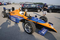 Indianapolis Colts corner back Kenny Moore II arrives in the back seat of a two-seat IndyCar driven by IndyCar driver Pato O'Ward as the players reported to the NFL team's football training camp in Westfield, Ind., Tuesday, July 27, 2021. Practice open on Wednesday. (AP Photo/Michael Conroy)
