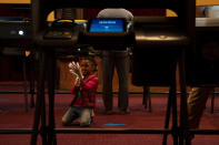 King Henry, 6, plays with his protective gloves while waiting for his grandmother to finish voting at the Hollywood Pantages Theatre on Election Day, Tuesday, Nov. 3, 2020, in Los Angeles. (AP Photo/Jae C. Hong)
