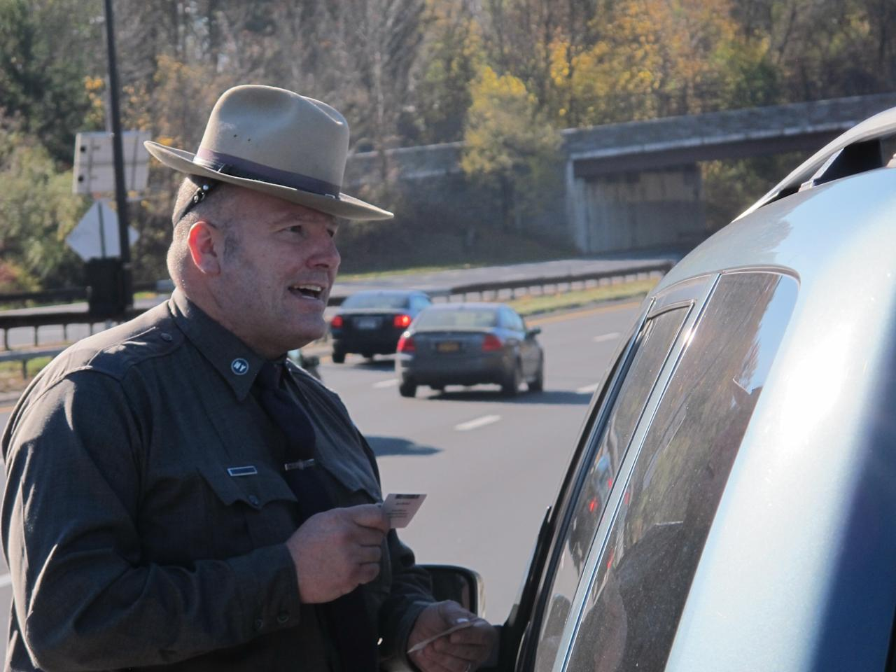 New York State Trooper Clayton Howell checks a driver's license after making a traffic stop for distracted driving in Greenburgh, N.Y., on Thursday, Nov. 14, 2013. Troopers are using a fleet of tall, unmarked SUVs as part of a crackdown on texting while driving. (AP Photo/Jim Fitzgerald)