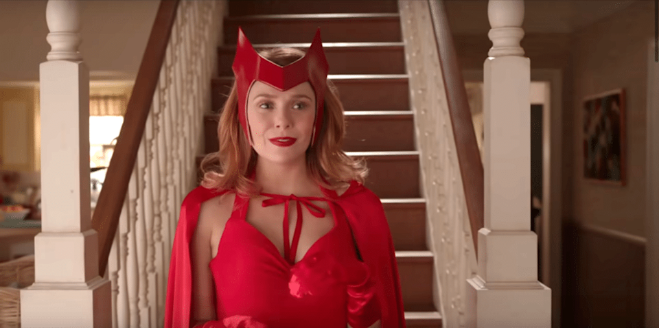 Wanda in a red dress, cape and headpiece