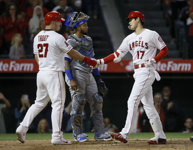 Los Angeles Angels designated hitter Shohei Ohtani, right, gets congratulations from Mike Trout after hitting a two-run home run, as Kansas City Royals catcher Martin Maldonado, center, looks away during the sixth inning of a baseball game in Anaheim, Calif., Saturday, May 18, 2019. (AP Photo/Alex Gallardo)