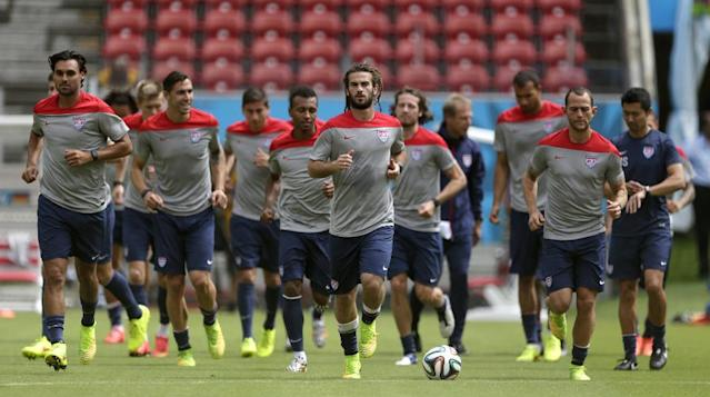 United States' Kyle Beckerman, center, jogs with teammates during a training session in Recife, Brazil, Wednesday, June 25, 2014. The United States will play Germany in group G of the 2014 soccer World Cup on June 26. (AP Photo/Julio Cortez)