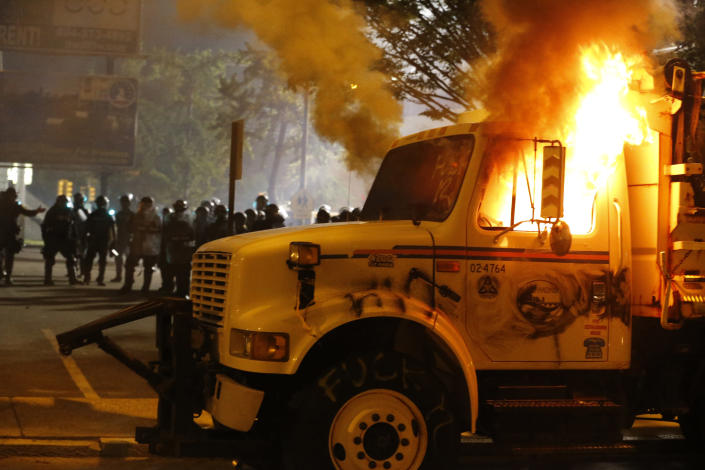 Police stand in front of a utility vehicle that was set on fire by protesters during a demonstration outside the Richmond Police Department headquarters on Grace Street in Richmond, Va., Saturday, July 25, 2020. Police deployed flash-bangs and pepper spray to disperse the crowd after the city utility vehicle was set on fire. (Joe Mahoney/Richmond Times-Dispatch via AP)