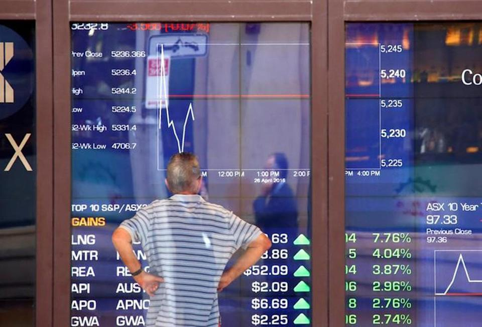 A man reacts as he looks at a board displaying stock prices at the Australian Securities Exchange (ASX) in Sydney, Australia, April 26, 2016. REUTERS/David Gray