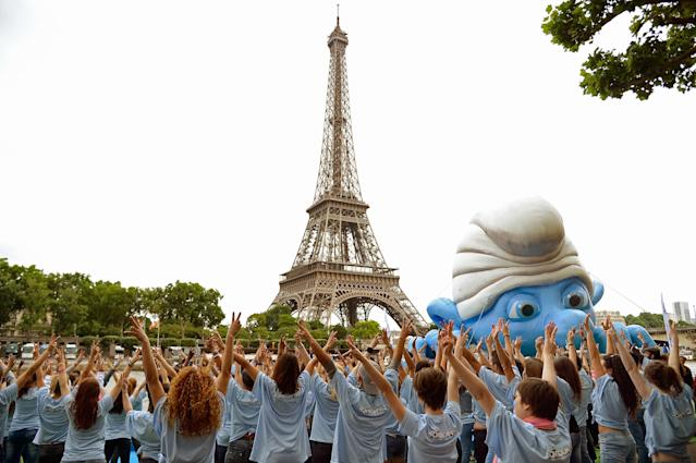 PARIS, FRANCE - JUNE 22: Dancers perform by a giant Smurf character as part of Global Smurfs Day celebrations on June 22, 2013 on the Seine river bank in Paris, France. (Photo by Pascal Le Segretain/Getty Images for Sony Pictures Entertainment)