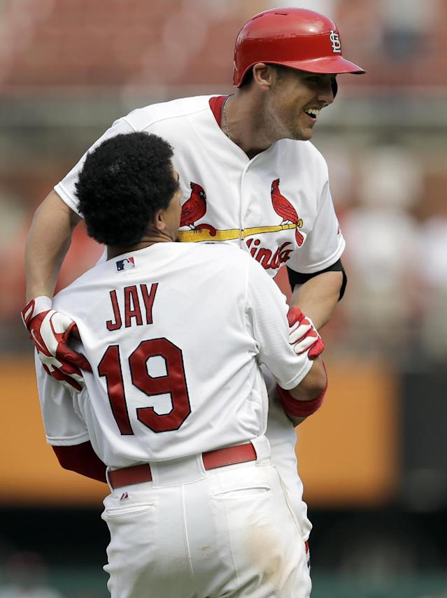 St. Louis Cardinals' Peter Bourjos, top, is congratulated by teammate Jon Jay (19) after hitting a walkoff-single to score Yadier Molina during the ninth inning of a baseball game against the Pittsburgh Pirates, Wednesday, Sept. 3, 2014, in St. Louis. The Cardinals won 1-0. (AP Photo/Jeff Roberson)