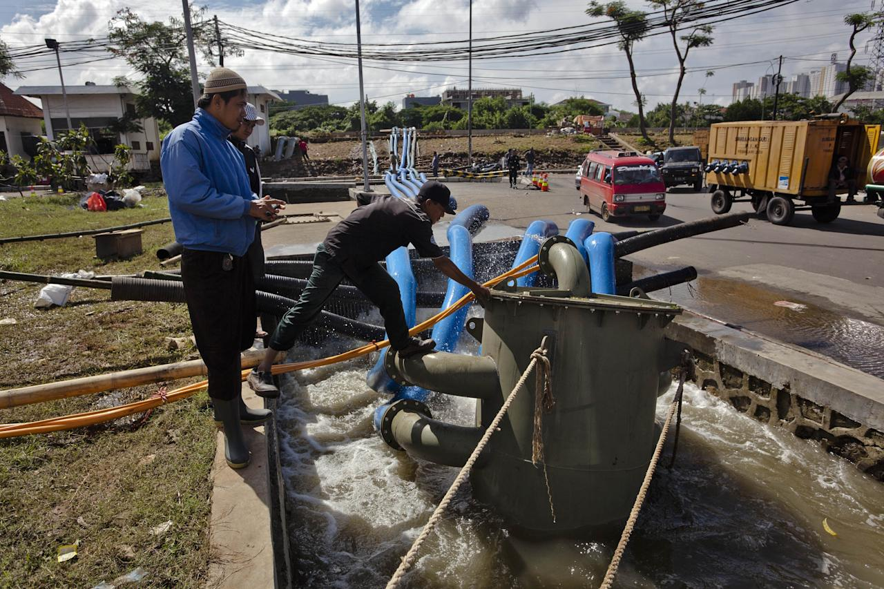 JAKARTA, INDONESIA - JANUARY 26:  Workers check on the water pump being as used to clean-up floodwaters in North Jakarta on January 26, 2013 in Jakarta, Indonesia. With heavy rain forecast for January 26-28, Indonesian authorities have organised the use of generators and cloud-seeding measures to defuse rain-laden clouds to help prevent further flooding of Jakarta, following last week's floods which claimed the lives of 32 people.  (Photo by Ulet Ifansasti/Getty Images)