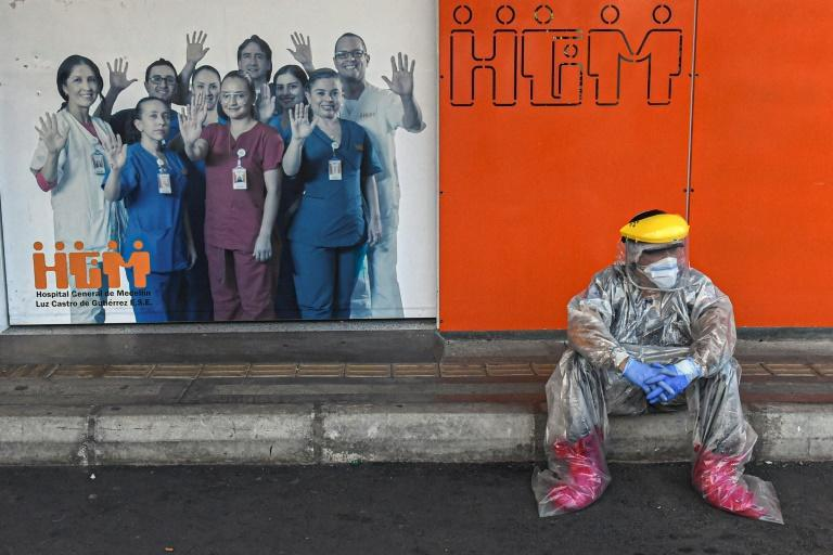 A Colombian health worker takes a break outside Medellin's General Hospital, amid the COVID-19 pandemic