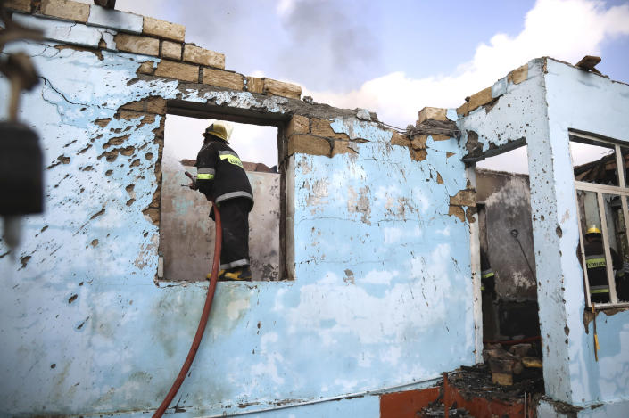 Azerbaijani firefighters work in damaged house after alleged recent shelling in a residential area in Agdam, Azerbaijan, on Thursday, Oct. 15, 2020. The conflict between Armenia and Azerbaijan is escalating, with both sides exchanging accusations and claims of attacks over the separatist territory of Nagorno-Karabakh. Heavy fighting is in a third week despite a cease-fire deal. (AP Photo/Aziz Karimov)