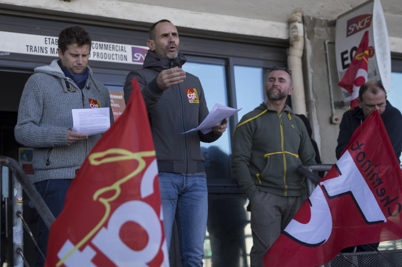 A striking railway worker speaks during a union general assembly meeting at the Gare St-Charles station in Marseille, southern France, Monday, Dec. 9, 2019. Paris commuters inched to work Monday through exceptional traffic jams, as strikes to preserve retirement rights halted trains and subways for a fifth straight day. (AP Photo/Daniel Cole)