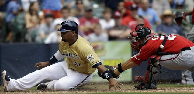 Milwaukee Brewers' Juan Francisco (21) slides safely past Washington Nationals catcher Kurt Suzuki (24) during the sixth inning of a baseball game Sunday, Aug. 4, 2013, in Milwaukee. Francisco scored from second on a single by Jeff Bianchi. (AP Photo/Morry Gash)