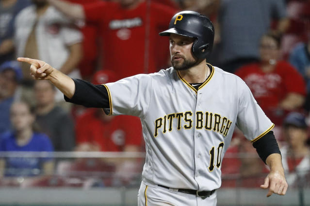 Pittsburgh Pirates' Jordy Mercer celebrates after scoring the go-ahead run on a triple by Josh Harrison off Cincinnati Reds relief pitcher Dylan Floro during the 12th inning of a baseball game Wednesday, May 23, 2018, in Cincinnati. (AP Photo/John Minchillo)