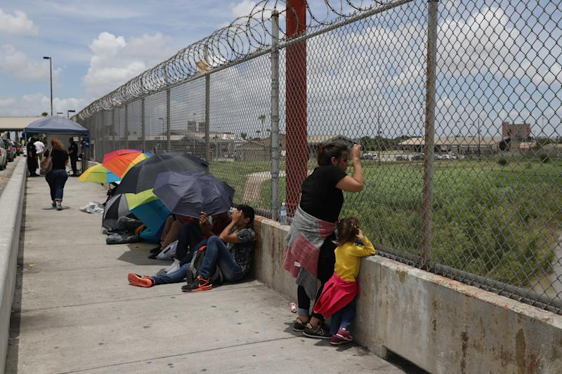 A Honduran mother and her 3-year-old daughter wait with fellow asylum-seekers on the Mexican side of the Brownsville-Matamoros International Bridge after being denied entry into the U.S.