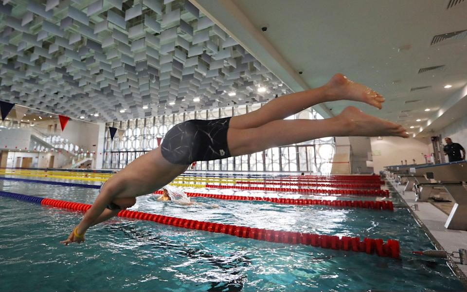 A visitor dives into a swimming pool at Aquatic Sports Palace, an aquatic centre which includes a water park, swimming pools and a surf point, at the Luzhniki Olympic Sports Complex - Getty Images