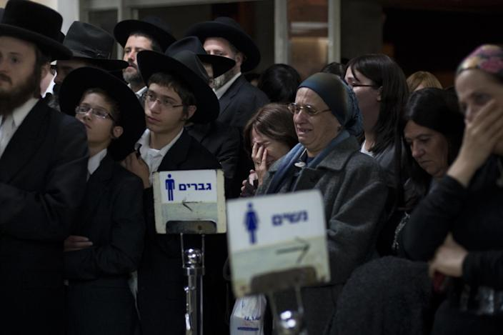 Ultra Orthodox Jewish men and woman attend the funeral of Mirah Sharf who was killed in the southern town of Kiryat Malachi by a rocket thought to have been fired by Palestinian militants from the Gaza Strip, in Jerusalem, Thursday, Nov. 15, 2012. Gaza militants led by the ruling Hamas Islamic group showered Israel with rockets Thursday in apparent retaliation for Israel's assassination of Hamas' powerful military chief a day before, and Israel's airforce struck dozens of Hamas-linked targets in Gaza with missiles on Thursday.(AP Photo/Sebastian Scheiner)