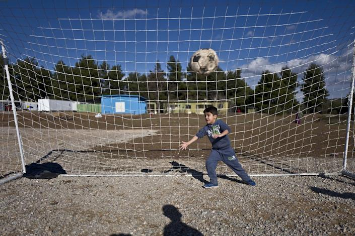 A Syrian refugee boy tries to catch the ball while he and others play soccer at the Ritsona refugee camp, about 86 kilometers (53 miles) north of Athens, Thursday, Jan. 5, 2017. Over 62,000 refugees and migrants are stranded in Greece after a series of Balkan border closures and an European Union deal with Turkey to stop migrant flows. (AP Photo/Muhammed Muheisen)