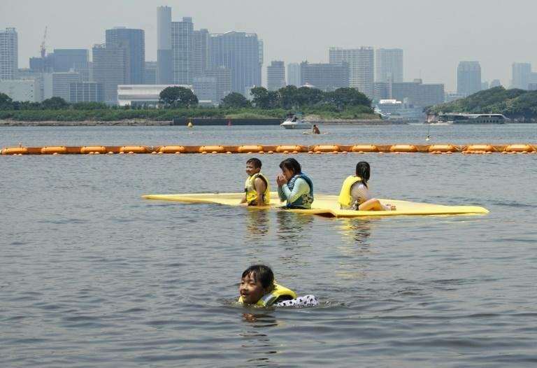 Children swim at Odaiba seaside park in Tokyo Bay with the skyline of the world's biggest city shimmering behind them