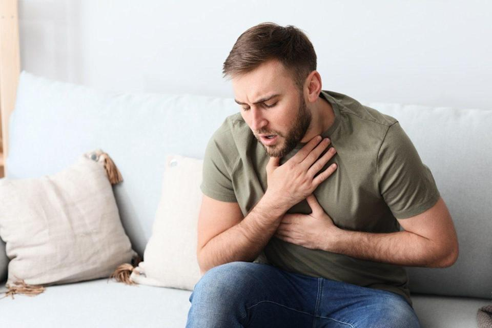 Young man having asthma attack at home