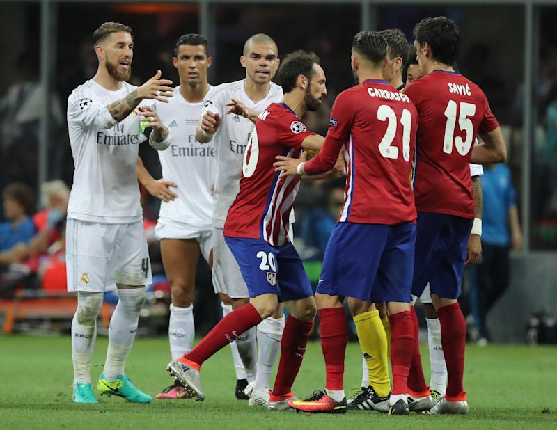 Atletico's Juanfran (C) agures with the referee Mark Clattenburg of England (hidden) next to Real's Sergio Ramos (L) Cristiano Ronaldo (2-L) and Pepe (3-L) during the UEFA Champions League Final between Real Madrid and Atletico Madrid at the Stadio Giuseppe Meazza in Milan, Italy, 28 May 2016. Photo: Christian Charisius/dpa | usage worldwide (Photo by Christian Charisius/picture alliance via Getty Images)
