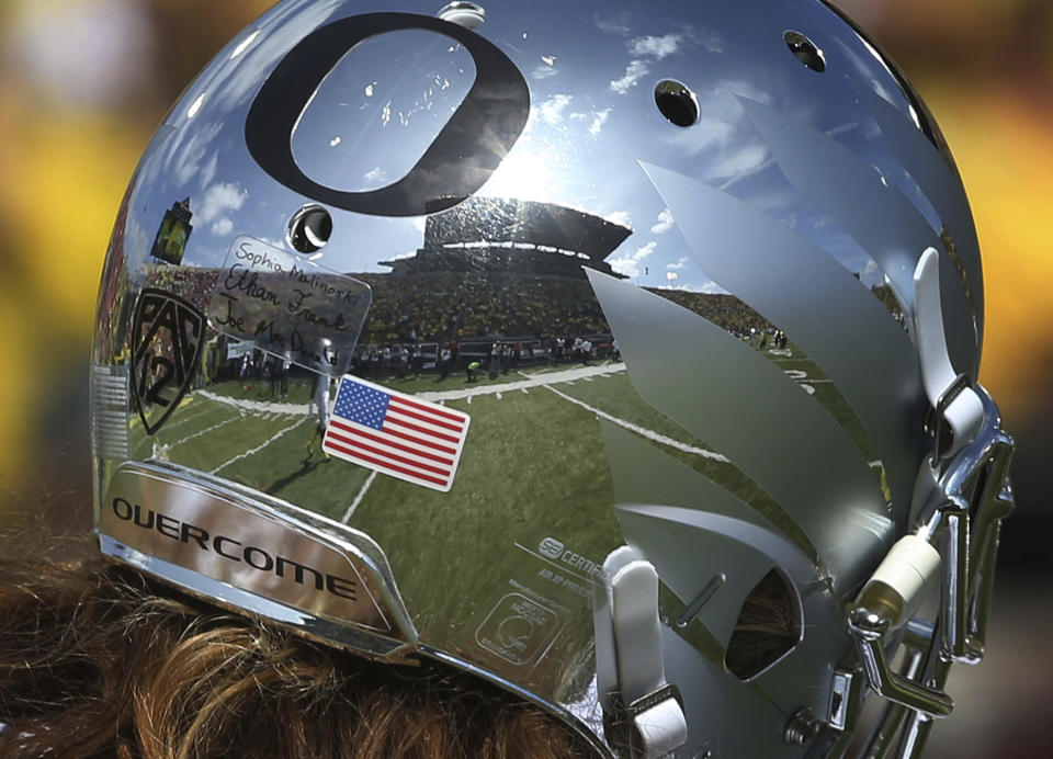 Autzen Stadium is reflected in the helmet of Oregon wide receiver Brenden Schooler during warmups before an NCAA college football game against Nebraska Saturday, Sept. 9, 2017, in Eugene, Ore. The uniforms were designed by a group of young cancer survivors from Doernbecher Children's Hospital in Portland, Oregon. (AP Photo/Chris Pietsch)