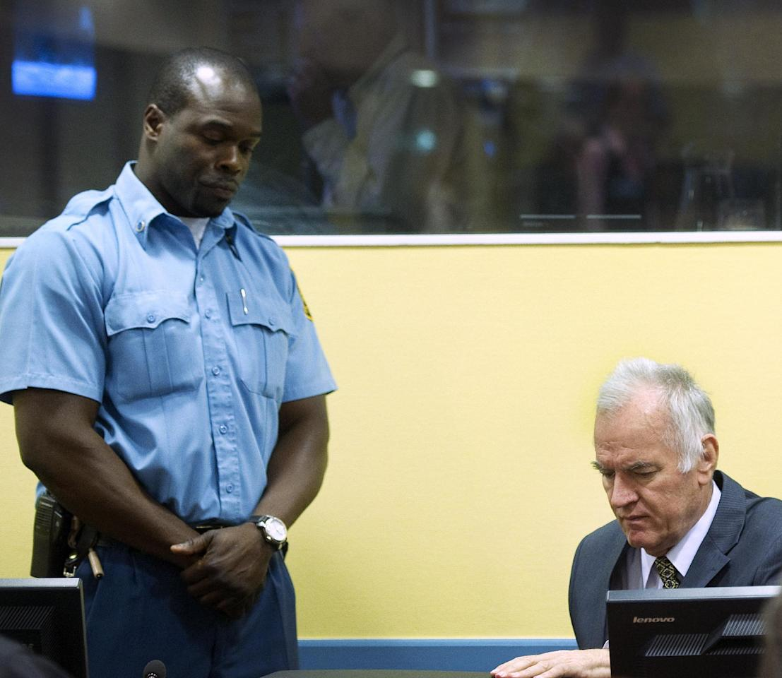 Former Bosnian Serb military commander Gen. Ratko Mladic, right, and a UN security guard, left, are seen at the start of his trial at the Yugoslav war crimes tribunal in The Hague, Netherlands, Wednesday May 16, 2012. Twenty years after the opening shots of the Bosnian War, Mladic has gone on trial on charges of genocide, crimes against humanity and war crimes, his appearance at the UN tribunal marks the end of a long wait for justice to survivors of the 1992-95 war that left some 100,000 people dead. (AP Photo/Toussaint Kluiters, Pool)