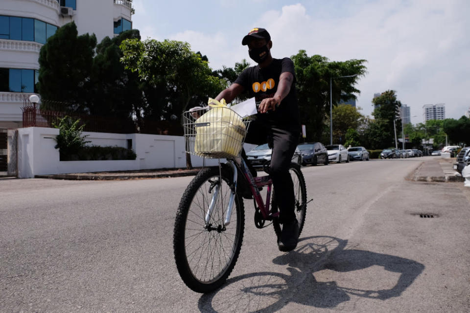 A delivery staff delivers the food to a nearby customer on bicycle. — Picture by Steven Ooi KE
