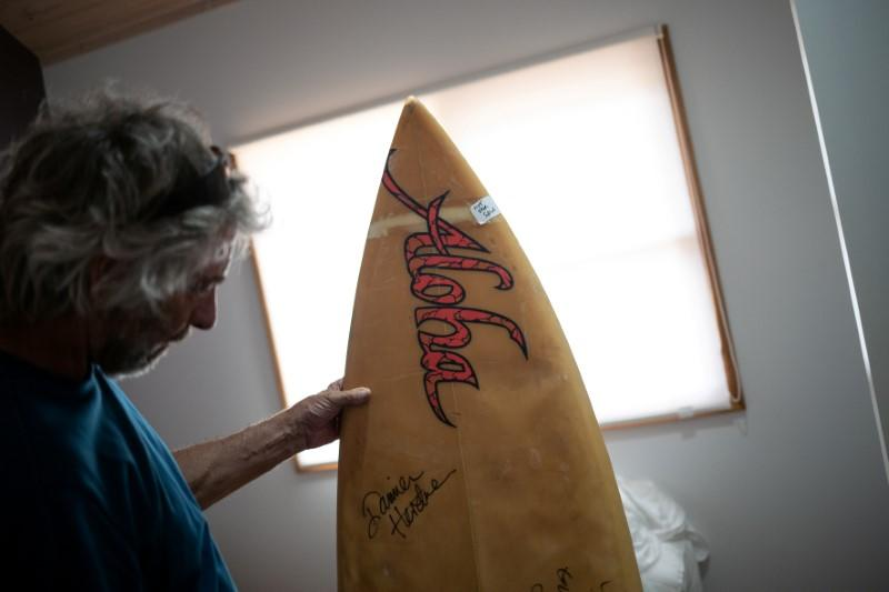 Australian surfer David Ford shows one of the few remaining surfboards of his vintage surfboard collection that was destroyed in the recent bushfires in Lake Conjola