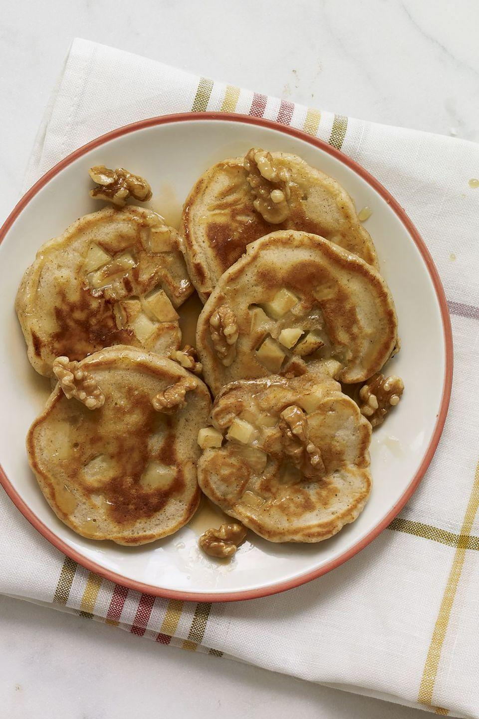 """<p>If Mom has a sweet tooth, start her Mother's Day off right with these pancakes that are packed with spice and topped with diced apples. </p><p><strong><a href=""""https://www.womansday.com/food-recipes/food-drinks/recipes/a12264/apple-pie-pancakes-maple-walnuts-recipe-wdy0113/"""" rel=""""nofollow noopener"""" target=""""_blank"""" data-ylk=""""slk:Get the Apple Pie Pancakes with Maple Walnuts recipe."""" class=""""link rapid-noclick-resp""""><em>Get the Apple Pie Pancakes with Maple Walnuts recipe.</em></a></strong></p>"""