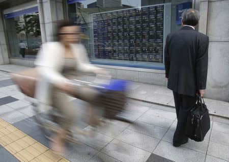A man looks at an electronic board showing various stock prices outside a brokerage in Tokyo
