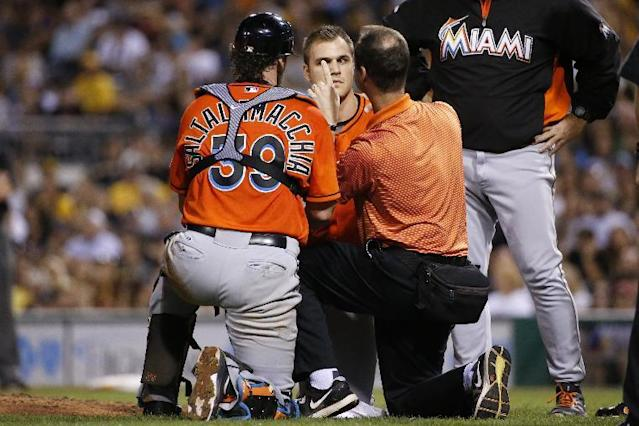 Miami Marlins relief pitcher Dan Jennings, center, is examined by a team trainer as he waits to be driven off the field after being hit by a line drive off the bat of Pittsburgh Pirates' Jordy Mercer during the seventh inning of a baseball game in Pittsburgh Thursday, Aug. 7, 2014. Jennings condition is not known at this time. (AP Photo/Gene J. Puskar)