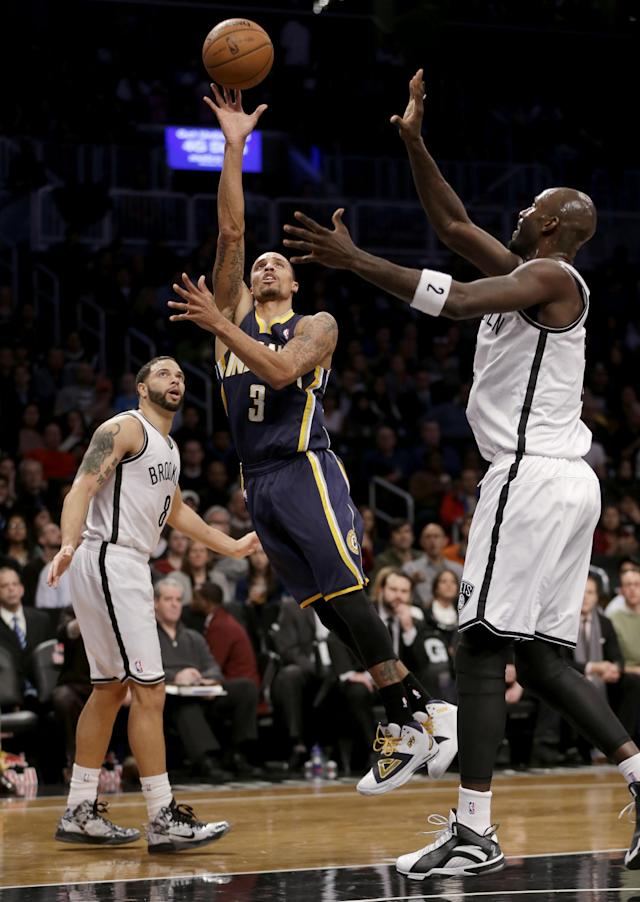 Indiana Pacers' George Hill, center, puts up a shot between Brooklyn Nets' Deron Williams, left, and Kevin Garnett during the first half of an NBA basketball game Monday, Dec. 23, 2013, in New York. (AP Photo/Seth Wenig)